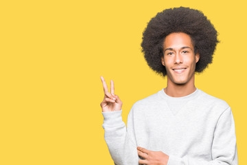 Young african american man with afro hair wearing sporty sweatshirt smiling with happy face winking at the camera doing victory sign. Number two.