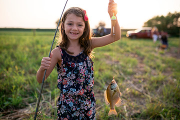 Portrait of smiling girl holding dead fish in fishing line