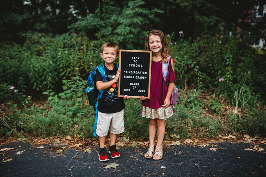 Full length portrait of smiling siblings with backpack and blackboard standing on road