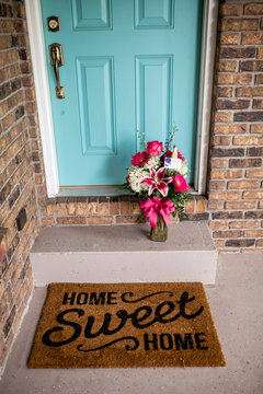 High angle view of bouquet on retaining wall by doormat against closed door