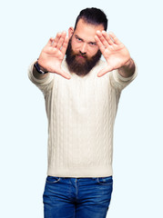 Young hipster man wearing winter sweater Smiling doing frame using hands palms and fingers, camera perspective