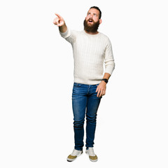 Young hipster man wearing winter sweater Pointing with finger surprised ahead, open mouth amazed expression, something in front