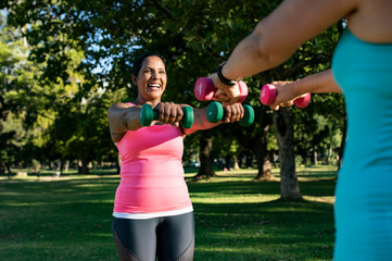 Happy female friends lifting dumbbells while standing against trees in park
