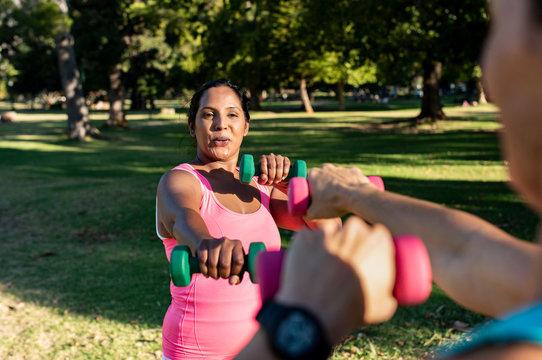 Female friends lifting dumbbells in park