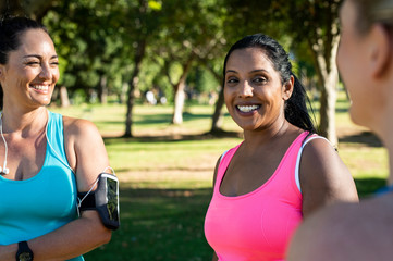 Happy female friends talking while exercising against trees in park