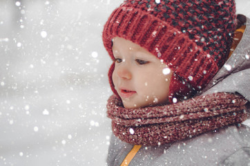 Portrait of a cute baby dressed in a gray jacket and a red hat that walks through the snow covered park  enjoying first snow blowing