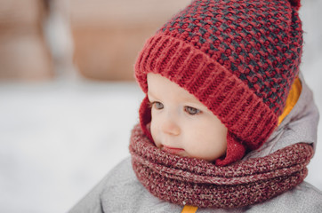 Portrait of a cute baby dressed in a gray jacket and a red hat that walks through the snow covered snow park. She smiles one in the photo during the snowfall