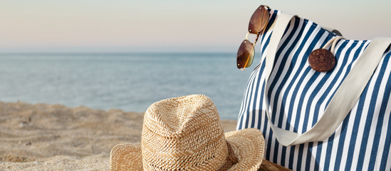 Striped summer bag with straw hat and sunglasses closeup on beach and calm sea background. Sunset time. Horisontal, copy space