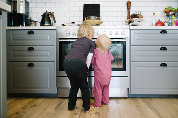 Rear view of sibling looking at oven in kitchen