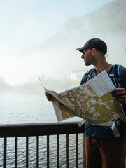 Hiker looking at lake while holding map by railing in forest