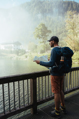 Side view of backpacker with map standing by lake in forest