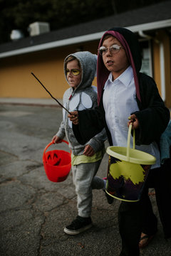 Full length of brothers dressed up as Harry Potter and owl walking on road with buckets during Halloween