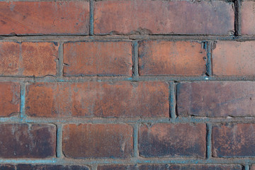 old large red brick wall with cement joints