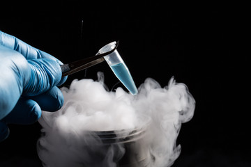 A scientist or lab personal freezes a tube filled with a light blue liquid in it