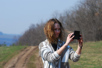 happy woman photographing herself outdoors