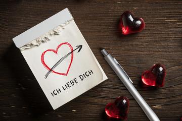 """Abreißkalender mit Herzsymbol und Nachricht """"Ich liebe Dich"""" auf  Holzhintergrund"""