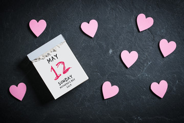 Tear-Off Calendar with Mothers's Day 2019 on top and decorative hearts on slate background
