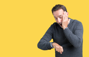 Handsome middle age senior man wearing a sweater over isolated background Looking at the watch time worried, afraid of getting late