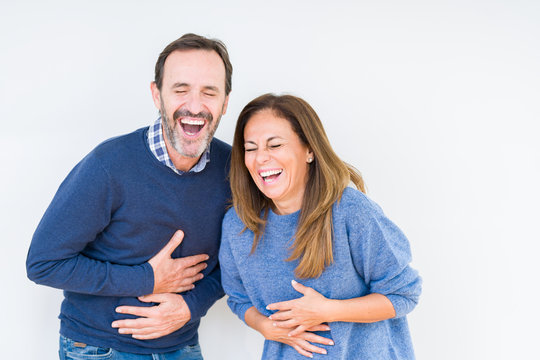 Beautiful middle age couple in love over isolated background Smiling and laughing hard out loud because funny crazy joke. Happy expression.