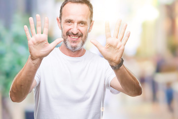 Middle age hoary senior man wearing white t-shirt over isolated background showing and pointing up with fingers number ten while smiling confident and happy.