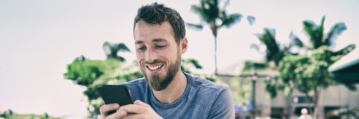 Smartphone man using mobile phone texting sms text message outside in summer background. Young people lifestyle banner panorama. Happy casual guy smiling holding cellphone using app for social media.