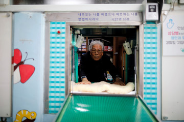 Lee Jong-rak, a senior pastor of Jusarang Community Church, poses for photographs through the baby box in which mothers can leave unwanted infants, at his church in Seoul