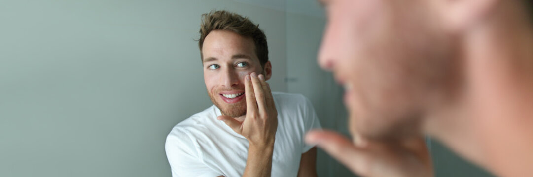 Man skin care putting moisturizer cream on face. Male beauty skincare concept. Young handsome adult looking in the bathroom mirror applying anti-aging lotion. Healthy lifestyle banner panorama.