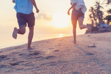 Young couple running along the sandy seashore in the rays of sunset, blurred image perfect background for travel agencies, honeymoon vacation travel in the tropics