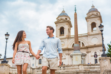 Wall Mural - Happy romantic couple holding hands on Spanish Steps in Rome, Italy. Joyful young interracial couple walking on the travel landmark tourist attraction icon during their romance Europe holiday vacation