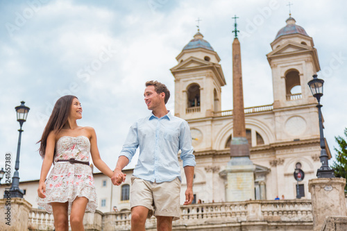 Wall mural Happy romantic couple holding hands on Spanish Steps in Rome, Italy. Joyful young interracial couple walking on the travel landmark tourist attraction icon during their romance Europe holiday vacation