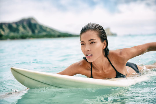 Surfing Asian woman surfer girl on surf lesson in Hawaii paddling on surfboard in ocean. Sexy sports athlete training in water. Watersport active lifestyle.