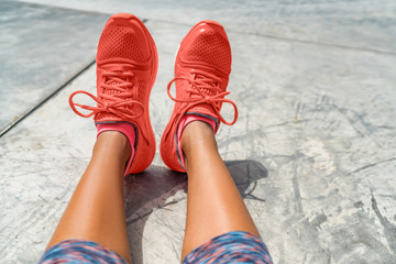 Running shoes woman fashion clothing in Pantone color of the year 2019 coral orange. Sporstwear sneakers for fitness clothes for women. POV selfie of feet on concrete floor at gym.