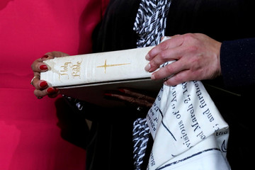 Rep. Lisa Blunt Rochester (D-DE) poses with a Bible for a ceremonial swearing-in picture on Capitol Hill in Washington