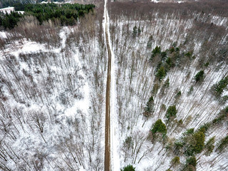 Aerial drone view of road in winter forest.