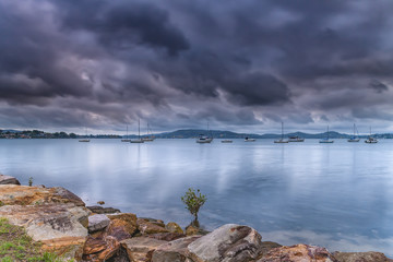 Grey cloudy skies and boats on the bay