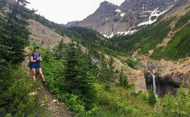 A young female hiker navigating the forests, rocky mountain terrain, and snow covered valleys of the Rocky Mountains on the Crypt Lake Trail, in Waterton Lakes National Park, Alberta, Canada.