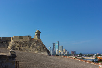 Observation tower of San Felipe de Barajas fortress with a view on modern cityscape of Cartagena, Colombia. Historic castle built on the Hill of San Lazaro and overlooking city of Cartagena de Indies.