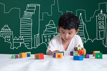 Asian kid learning by playing with his imagination about building and engineer architecture drawing and designer, hand drawn on the green chalkboard, education back to school concept.