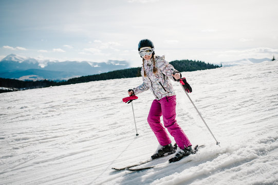 Happy woman in glasses go skiing on skis on snow in Carpathian mountains. On background of forest and ski slopes. Close up. Winter nature.