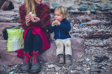 Mother and toddler eating sandwiches on the beach