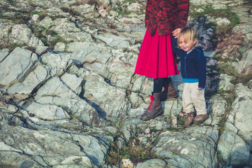 Mother and toddler relaxing on rocks