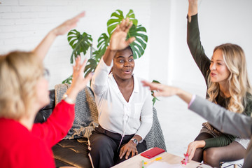 Multiracial young creative female freelancers meeting in modern office. Successful female creative team elebrate successful jump in sales growth