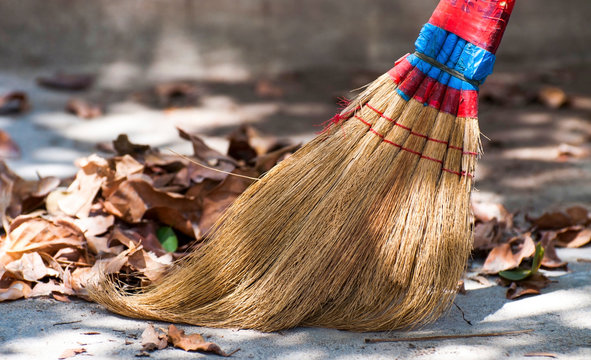 broom and autumn leaves