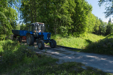 SOLOVKI, REPUBLIC OF KARELIA, RUSSIA - JUNE 25, 2018:Tractor with trailer moving along a forest road  on Solovki Island. Solovetsky archipelago, Arkhangelsk Region, Russia