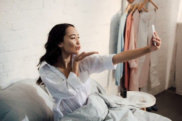 attractive asian woman blowing kiss and taking selfie with smartphone in bed