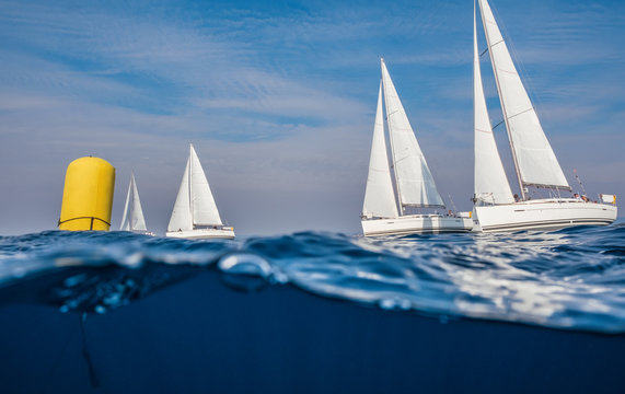 Underwater view on sailing boats with yellow buoy racing at open sea