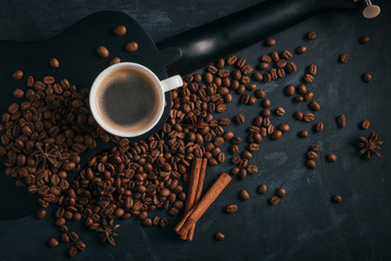 A cup of coffee is on a black ululele with scattered coffee beans, anise and cinnamon