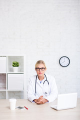 portrait of young female doctor sitting in office - copy space over white wall
