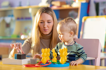 Preschool child, playing with toys in a sunny room, kid development