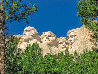 Mount Rushmore National Memorial is a sculptural rock complex in South Dakota, Black Hills, made up of huge granite blocks. The presidents are: Washington, Jefferson, Roosevelt, and Lincoln. Blue sky.